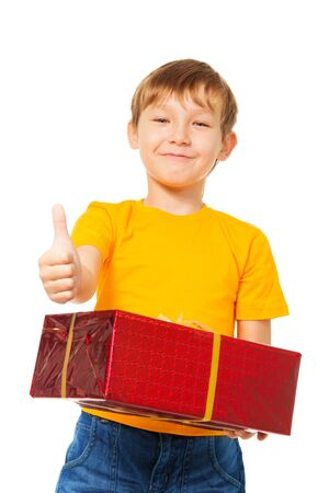 8 years birthday: Happy cute boy standing with present and holding his thumb up Stock Photo