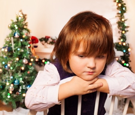 christmas eve: Sad kid sitting with Christmas tree and fire place on the background sad as Christmas is over