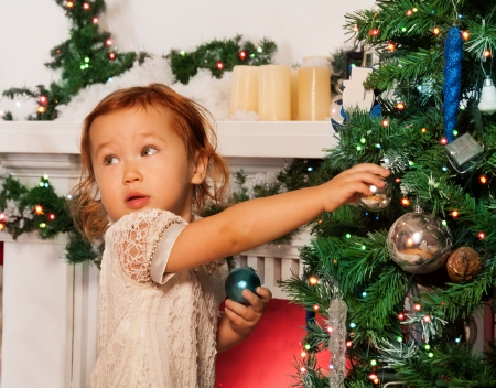 decorating: Little girl decorating Christmas tree with glass balls with fireplace on the background