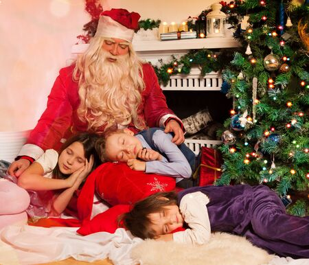Santa Claus and sleeping kids near decorated tree and fireplace photo