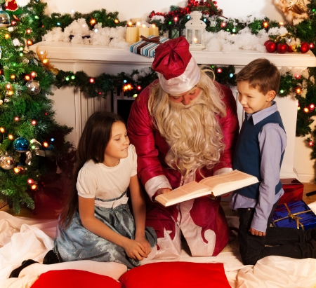 Santa reading Christmas book to kids sitting by decorated tree with boy and girl Stock Photo