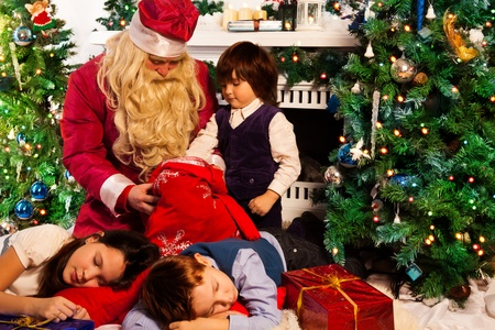 three presents: Kid looking for presents in Santas bag with presents while his siblings are slipping Stock Photo
