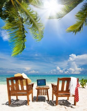 silla: Sillas, portátil y guardar cuello de corbata y camisa blanca, sombrero de paja. Sillas y mesa en la playa en un día soleado