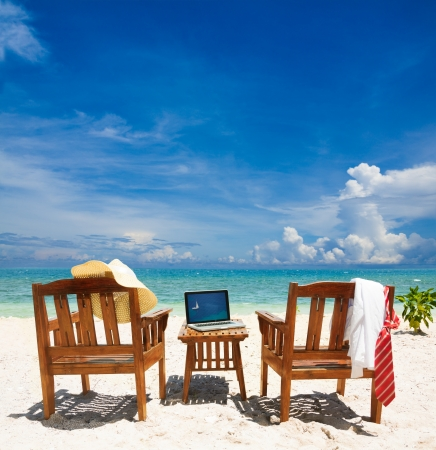 Chairs, laptop and put away tie and white collar shirt. Chairs on the beach on sunny day Stock Photo