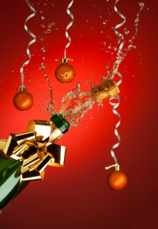 Popping cork from Champaign bottle with Christmas balls on background photo