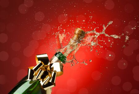 popping cork: Popping cork from Champaign bottle with lots of splashes red background Stock Photo