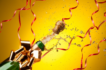 Popping cork from Champaign bottle with gold bow and ribbons on background, with splashes all around the yellow background photo