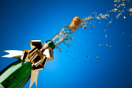 Popping cork from Champaign bottle with gold bow on it and splashes all around the blue background