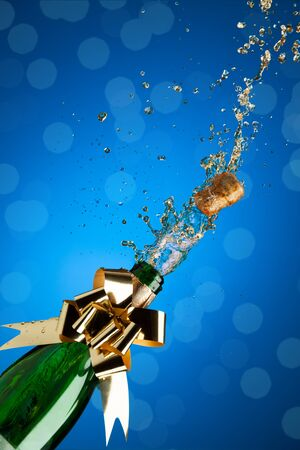 Champagne splashes from bottle and popping cork on blue background photo