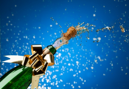 Popping cork from Champaign bottle with gold bow on it and splashes all around the blue background photo