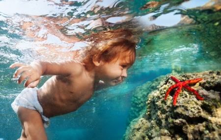 discover: Two years old boy diving underwater to see red starfish Stock Photo