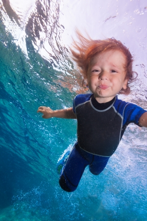 funny little kid swimming underwater in wetsuit photo