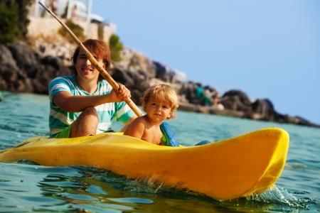 ocean kayak: Padre con hijo pequeño remo en kayak en el mar