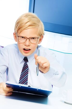 Teen blond boy  with strong expression gesticulating that he is the boss as he plays and adult businessmen Stock Photo - 17420403