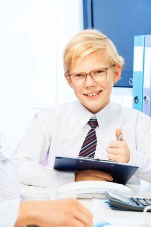 11 years old kid playing adult businessmen signing a contract, sitting in the office with his partners and with smile on his face Stock Photo - 17420396