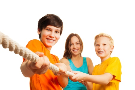 13: Three teen friends pulling the rope, trying to win competition Stock Photo