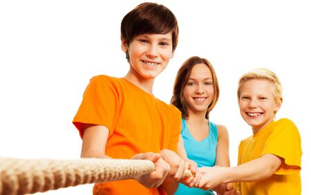 Teamwork - three kids pulling the rope with smile Stock Photo - 17445135