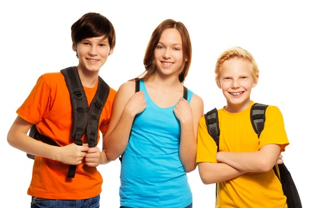 young boy smiling: Three kids with school backpacks standing together