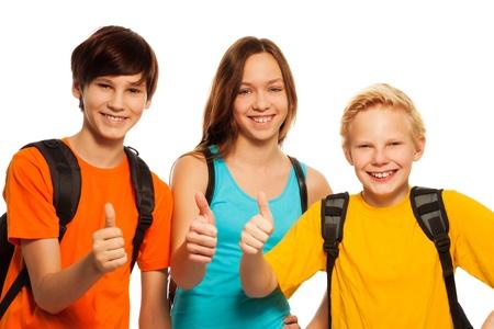 Szczęśliwe dwóch chłopców i dziewczyna wykazujące Kciuki gest noszenia plecaków szkolnych, odizolowane na białym