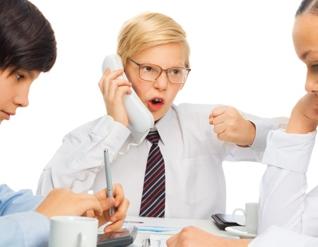 Kid playing angry businessman adult rearing to telephone as he sits on a meeting with his employees Stock Photo - 17420719