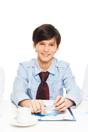Smart happy boy pretending to be a businessman as his parents by sitting in the office and wearing formal shirt wiht tie photo