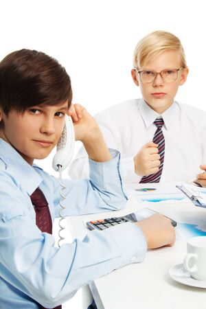 Two kids sitting by the table playing adults and doing business wearing formal shirts with tie photo