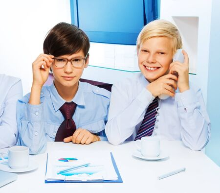 Two smart kids in the office playing to be and adults and discussing business topic as they play adults photo