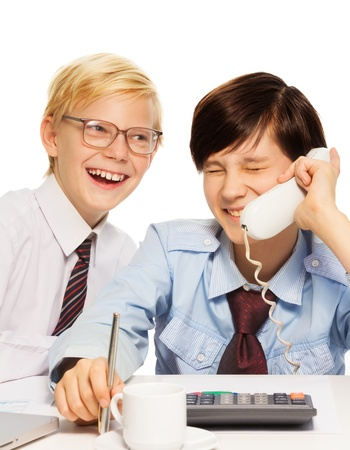 Two kids playing adult businessmen joking and laughing on the phone photo