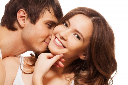 young couple hugging kissing: Young adult woman smiling and holding hand near mouse with boyfriend kissing her