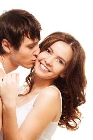 kiss couple: Young man kissing his happy smiling girlfriend isolated on white