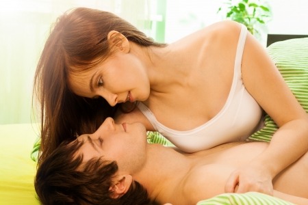 closeness: Beautiful woman and her husband playing in the bed Stock Photo