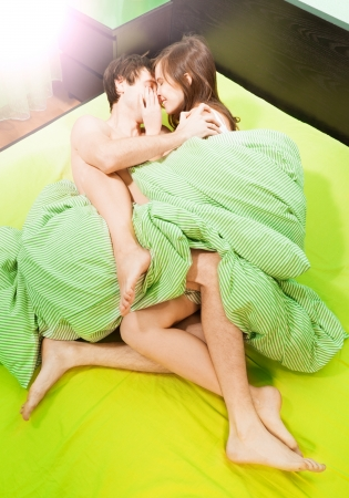 women kissing women: Happy sexy beautiful couple making love in bed Stock Photo