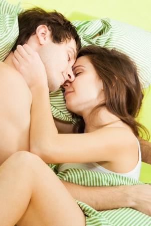 Pareja dormir juntos en la cama con una sonrisa en sus caras photo
