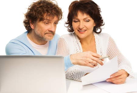 Old couple discussing some paper witting by computer Stock Photo - 17421808