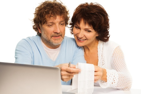 Senior couple smiling and discussing receipt  sitting by computer photo