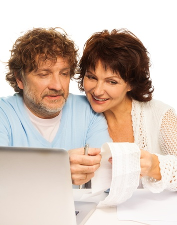 Senior couple smiling and holding receipt sitting by computer photo