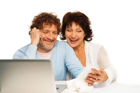 Senior couple laughing and holding receipt sitting by computer photo