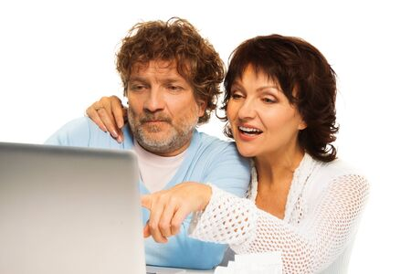 Senior couple sitting by computer with wife pointing to the screen photo