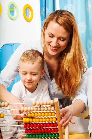 Mother and her little son learning math with abacus Stock Photo - 17421893