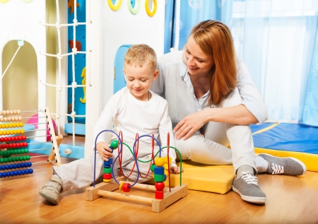 Mothers and her little blond boy learning to solve puzzle with toys Stock Photo - 17421828