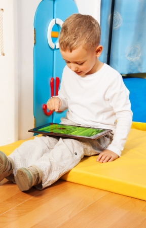 occupied: Blond five years old boy occupied with tablet computer touching screen with finger