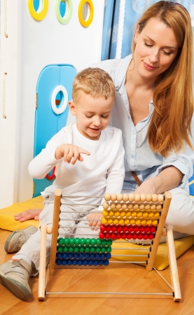 Mother and her little son learning math with abacus photo