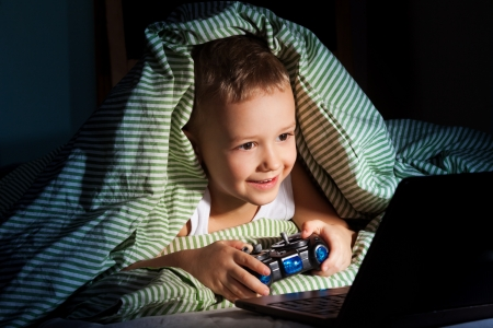 sneak: five years old happy kid hiding under blanket playing computer games