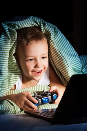 Young five years old boy hiding from mom under blanket playing computer games Stock Photo - 17421894