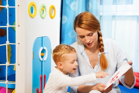 Mom showing his son screens with letters teaching alphabet Stock Photo - 17421799