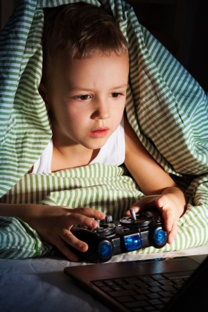 Little five years old boy playing games on computer with gaming console photo