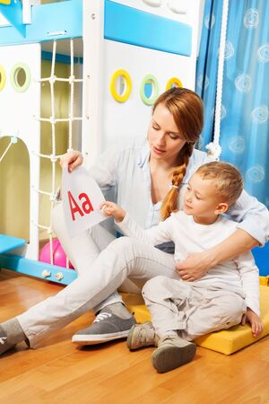 Mother and the son learning alphabet by showing slides with letters sitting in the corner of the room photo