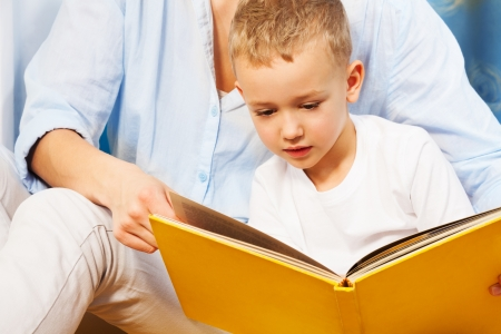 5 years: Five years old boy reading a book with his mother Stock Photo