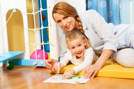 Mother and child drawing together laying on the floor in bedroom Stock Photo - 17421824