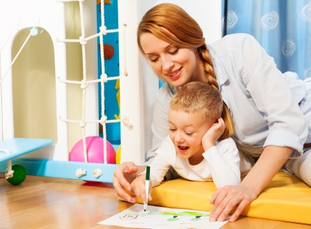 Blond happy five years old child drawing with mother laying on the floor in bedroom Stock Photo - 17421801